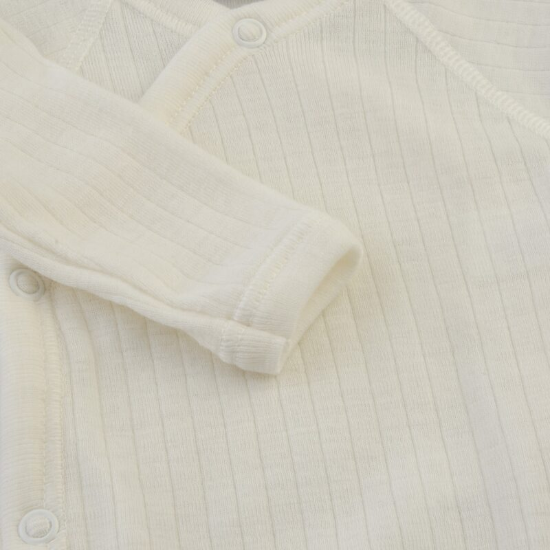Langærmet body til for tidligt født. Hvid svanemærket merinould. Detalje af ærme.