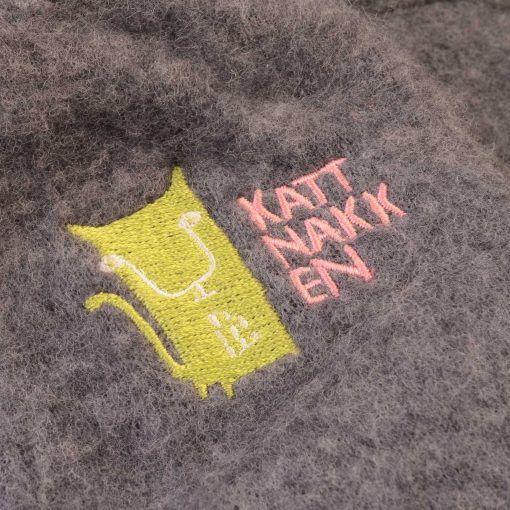 Køredragt i mørkegrå softuld med hætte fra Kattnakken. Detalje af mærke.