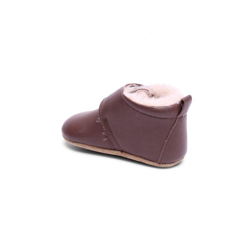 Hjemmesko i brun læder med uldfor. Velcrolukning og ruskindssål med skridsikker gummi. Hælkappen er forstærket og fast, så barnet støttes når de første skridt tages.