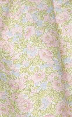Blomstret kjole til pige. Fin kjole uden ærmer og med blomstret motiv og blondekanter. Her ses blomstermønstret tæt på.