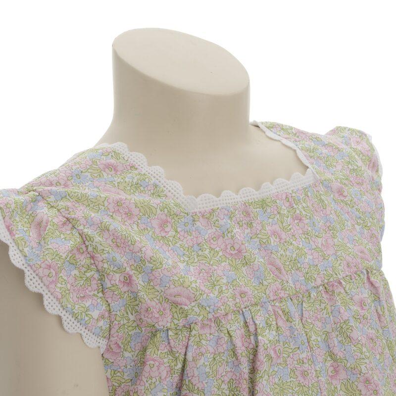 Blomstret kjole til pige. Fin sommerkjole med korte ærmer og med blomstret motiv og kniplingkanter. Her ses kniplingkanter ved ærmer og hals.