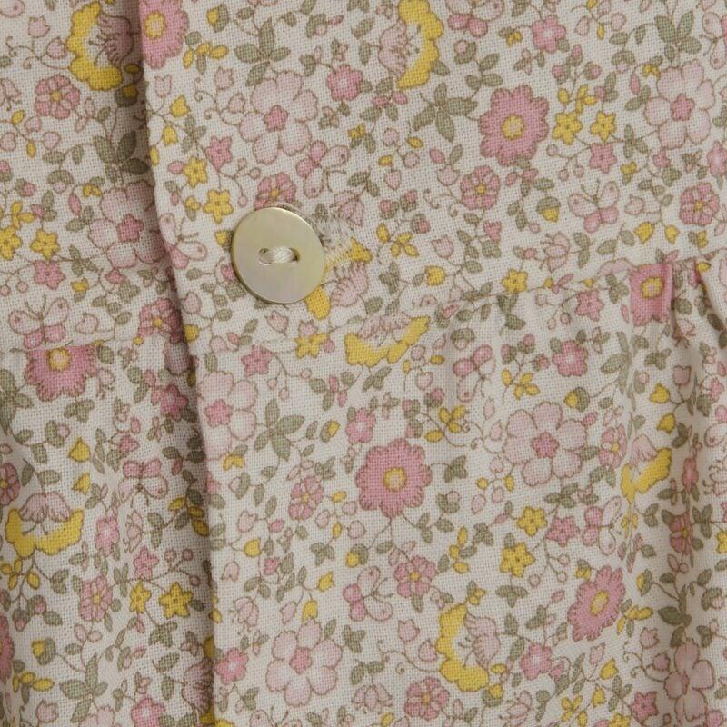 Bluse i blomstret mønster. Sommerbluse i gul og lyserødt mønster. Detalje af mønster og knap. Alerin.